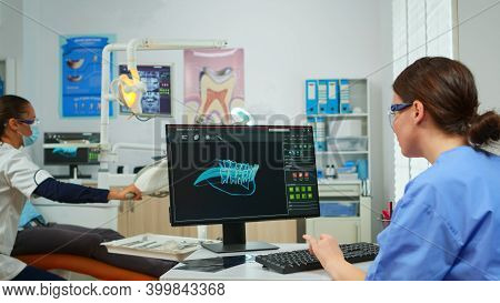 Nurse Working At Digital Dental Fingerprint Of Patient, While Specialist Dentist Doctor With Face Ma