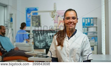 Stomatologist Doctor Smiling At Camera In Dental Office While Assistant Preparing Man For Stomatolog