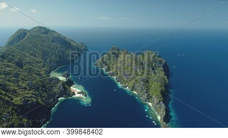 El Nido Islands at blue sea bay aerial view. Green mountain isles with tropical forest at sand beach. Wonderful seascape with greenery islets of Philippines Archipelago. Cinematic drone shot