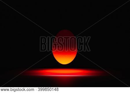 Red Egg Levitating Over A Black Glass Table In The Dark Room.