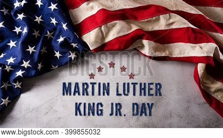 Martin Luther King Day Anniversary Concept. American Flag Against Dark Stone Background