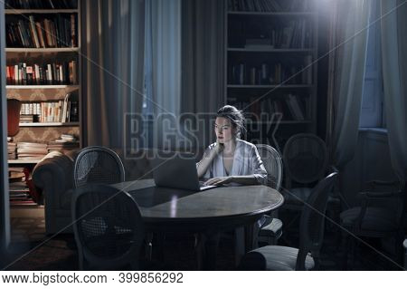 young woman works with computer in the evening at home