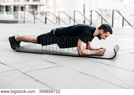 Plank It Training In Big City Concept. Sporty Young Man Wearing Black Sportswear And Doing Plank Pos