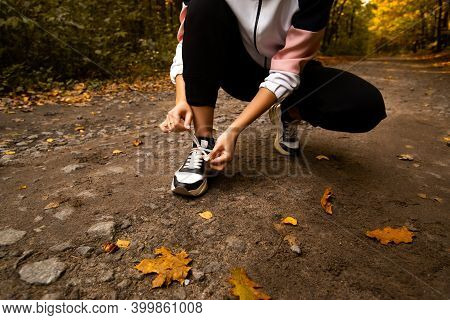 Womans Hands Fixing Shoelaces On Her Sneakers. Close Cut View. Female Trail Runner. Morning Run Conc