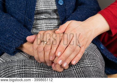Close Up Picture Of Old Woman Trembling Wrinkled Hands, Caregiver Holding Her