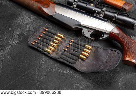 Close Up Of Hunting Shotgun And Cartridges On Dark Grey Background