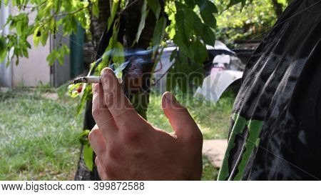 Cigarette Smoking In Fingers Of Young Adult Man Hand. White Smoke From Smoldering Cigarette Holding