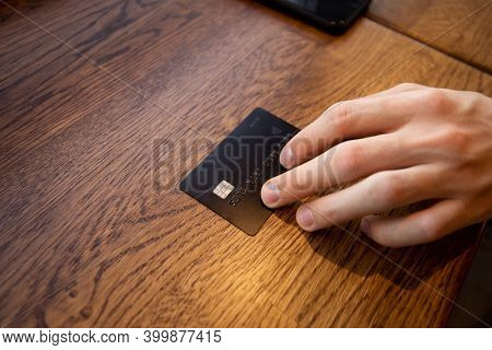 Black Credit Card Close Up. Male Hand Gives A Card To Pay Off The Bill. You Can Buy Anything Concept