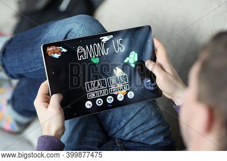 Minsk, Belarus - December 15 2020: Man Holding Tablet With Game Among Us Closeup. Illustrative Edito
