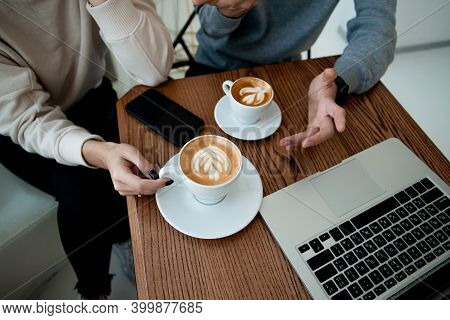 Womans And Mans Hands Holhs Cups Of Cappuccino Or Flat White. Top Cut View. Modern Laptop On Wooden