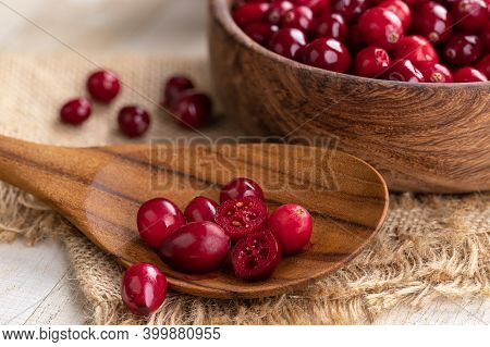 Fresh Cranberries On A Wooden Spoon With Bowl Of Cranberries In Background