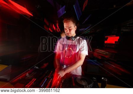 Disk Jockey Drives The Crowd. Blurred Man In White T Shirt And Headphones Mixes Tracks With Turntabl