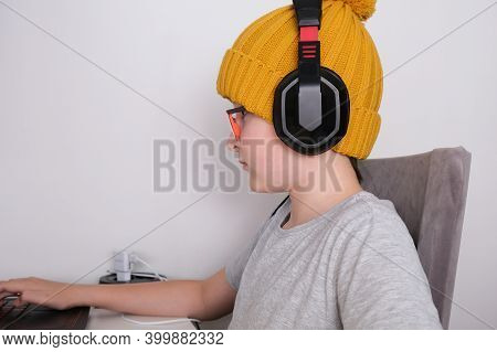 A Gamer Boy In A Trendy Knitted Cap And Heaphones Sitting By The Table And Playing Multiplayer Compu