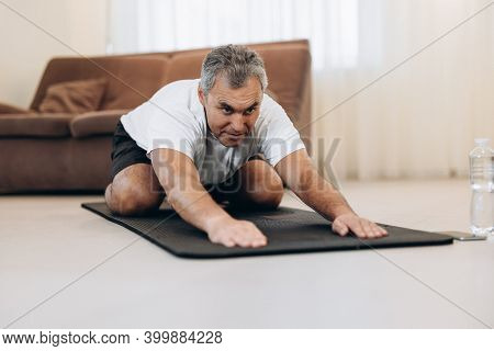 Old Man In Sportswear Lying On Mats Doing Child Asana, Exercise Calms Body And Mind, Stretching Hand