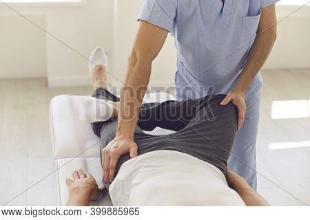 Hands Of Professional Man Chiropractor Manual Therapist Fixing Man Patients Pelvic Bones