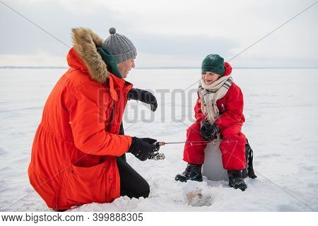 A Little Boy In A Red Jumpsuit And Scarf Is Fishing In An Ice Hole With His Father.