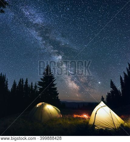 Night Camp With Burning Bonfire And Two Tents In Pine Forest Under Bright Starry Sky On Which Milky