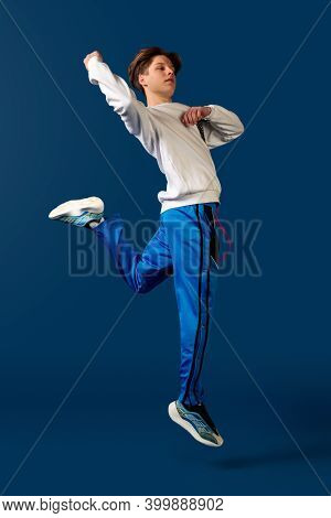 Jumping. Old-school Fashioned Young Man Dancing Isolated On Blue Studio Background. Artist Fashion,