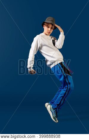 Balancing. Old-school Fashioned Young Man Dancing Isolated On Blue Studio Background. Artist Fashion