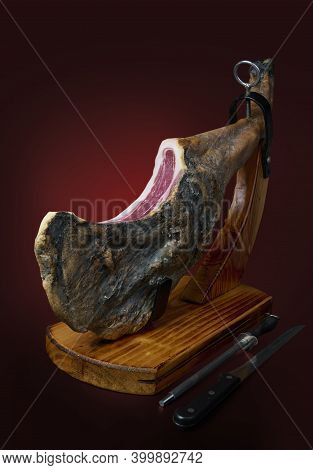Spanish Iberian Serrano Ham In Wooden Support. Isolated On Red Dark Background