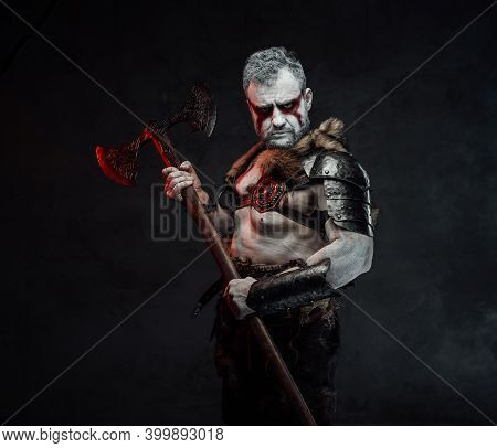 Artistic Portrait Of A Mythical Warrior With Painted Skin In Light Armour With Fur Posing In Dark Ba