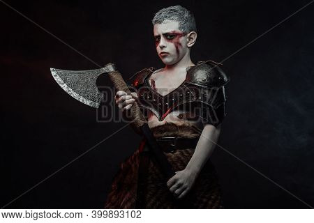 Portrait Of A Kid With Painted In White Skin Dressed In Dark Armour And Olding Axe In Dark Backgroun