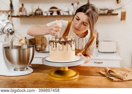 Beautiful focused pastry chef woman making cake with cream at cozy kitchen