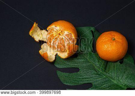 Tangerines On A Black Background. Citrus Fruit. Tangerines On A Green Leaf. One Of The Tangerines Pe