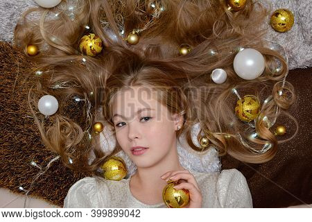 A Beautiful Young Girl In A Shiny Dress Lies Among The Gold And White Christmas Balls And Garlands O
