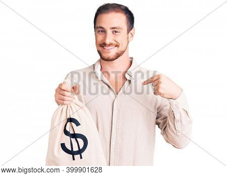 Young handsome caucasian man holding money bag with dollar symbol pointing finger to one self smiling happy and proud