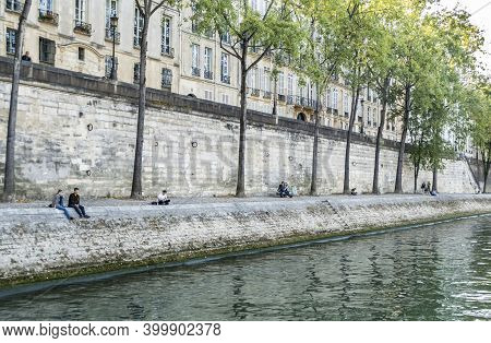 Paris, France - 09-12-2018:  Young People Sitting On The Bank Of The Seine