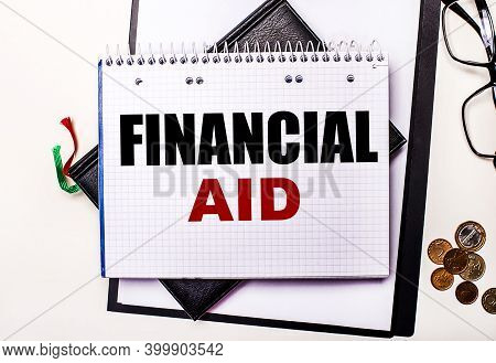 On A Light Background Glasses, Coins And A Notebook With The Inscription Financial Aid. Business Con
