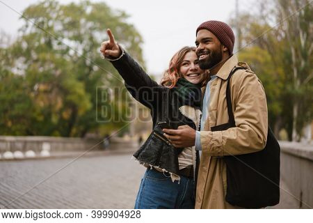 Multinational joyful couple pointing finger aside and using mobile phone at city street