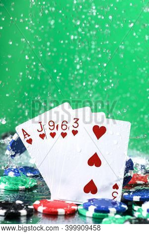 Flush Poker Combination Under The Water Drops And Falling Poker Chips Against Green Background. Onli