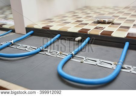 Installing A Radiant Floor Heating System With A Close Up Of Heating Cables Fastened To The Floor Un