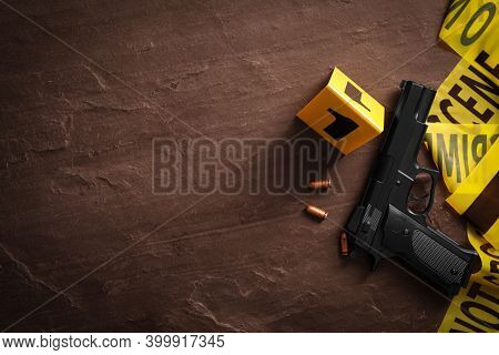 Flat Lay Composition With Gun And Bullets On Black Slate Background, Space For Text. Crime Scene