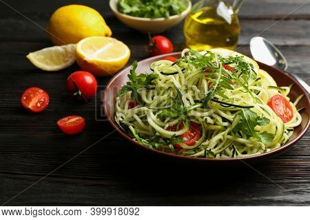 Delicious Zucchini Pasta With Cherry Tomatoes And Arugula Served On Black Wooden Table