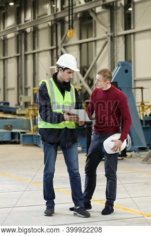 Young Men, Factory Engineer And Chef Engineer In A Work Dress And White Hard Hat Holding Smartphone