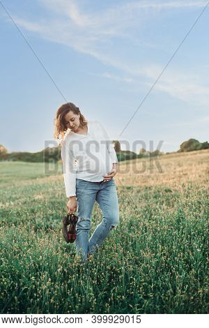 Pregnant Woman Expecting Baby In Cowboy Wear At Sunset.