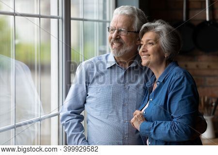 Happy Bonding Loving Middle Aged Couple Looking Out Of Window.