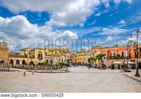 Matera, Italy - May 6, 2018: People Tourists Walking Down Piazza Vittorio Veneto Square With Stone B