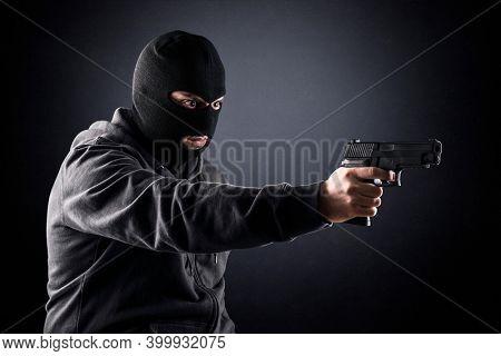 Criminal wearing black balaclava and hoodie with a gun in the dark