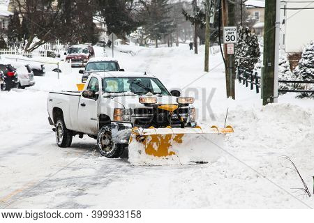 NORWALK, CT, USA-DECEMBER 17, 2020: Snow plowing truck on Taylor Avenue after winter snow storm.