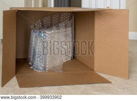 Humorous Photo Of A Small Boxed Product Surrounded By Bubble Wrap In A Large Almost Empty Delivery B