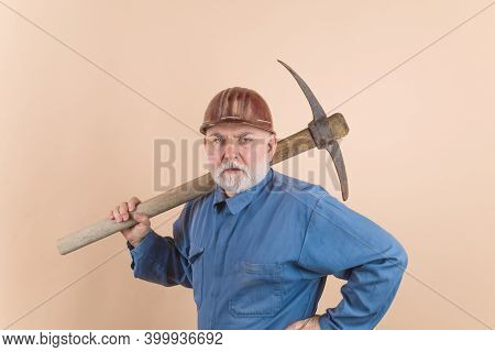Bricklayer In Hard Hat With Pickaxe. Construction Worker Holds Pickaxe. Man Contractor With Axe. Wor