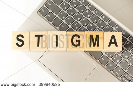 Word Stigma. Wooden Cubes With Letters Isolated On A Laptop Keyboard. Business Concept Image.