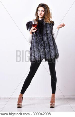 Fashion Model Long Hair Fur Coat Or Vest Hold Wineglass. Woman Drink Wine Wear Luxury Fur Clothing.