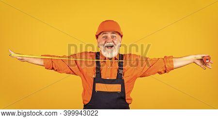 Confident Mechanic. Happy Carpenter. Handyman Measuring Wall. Senior Builder Tape-line For Measure.