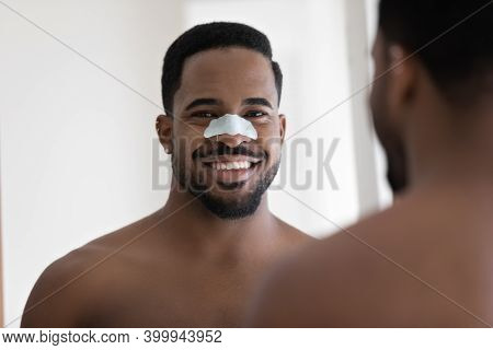 Happy African Ethnicity Man Cleansing Pores With Removal Strip.