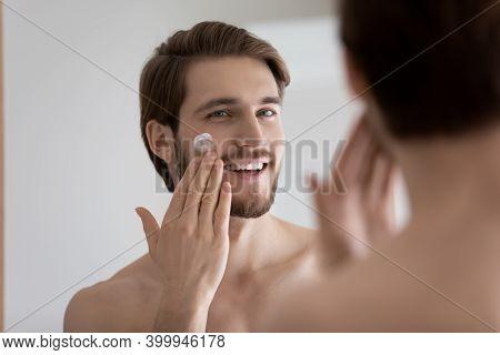 Smiling Handsome Man Applying Moisturizing Creme In Bathroom.